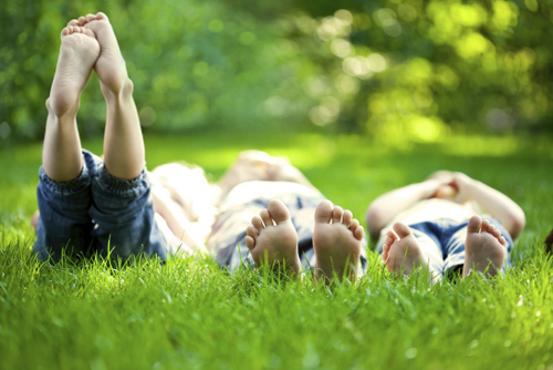 A picture of three kid laying down in the grass. Learn more about lawn care maintenance and our landscaping services at Water-Rite, in Vancouver, WA